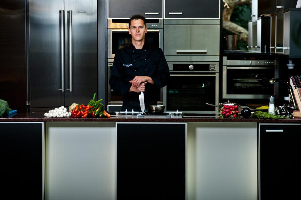 Koch Mathias Schumann steht in der Küche und stützt sich auf Messer ab