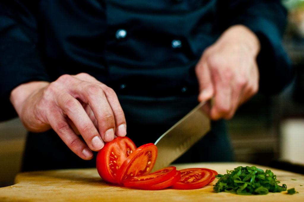 Nahaufnahme Koch schneidet Tomate